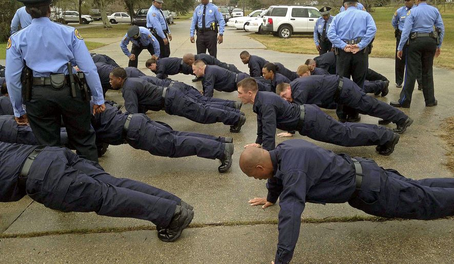 "Police trainers bark at recruits who struggle to execute the ""perfect push up"" for the New Orleans Police Department's newest recruiting class comprising of 29 new recruits and one lateral start in New Orleans, La., Monday, Jan. 12, 2014. (AP Photo/The Advocate, Benjamin Oreskes)  MAGS OUT; INTERNET OUT; NO SALES; TV OUT; NO FORNS; LOUISIANA BUSINESS INC. OUT (INCLUDING GREATER BATON ROUGE BUSINESS REPORT, 225, 10/12, INREGISTER, LBI CUSTOM); MANDATORY CREDIT"