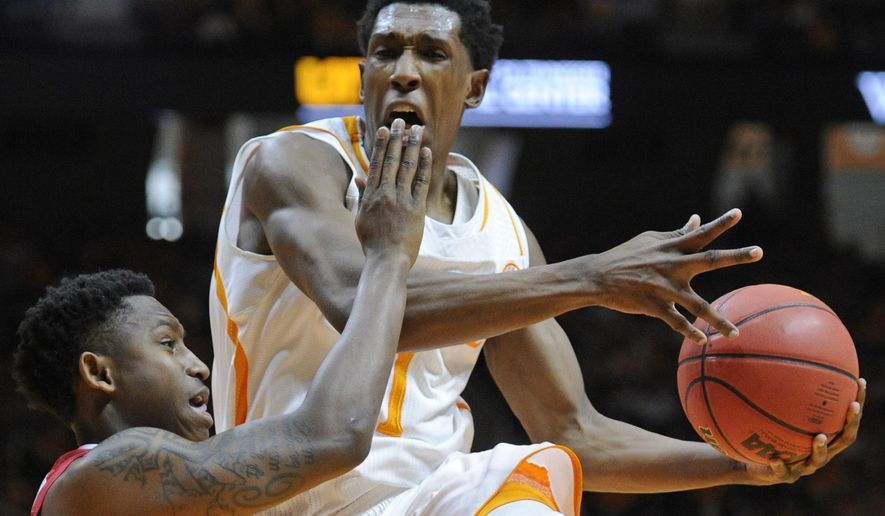 Tennessee guard Josh Richardson (1), center, is fouled by Alabama guard Justin Coleman (5), left, while attempting a layup during the first half of an NCAA basketball game at Thompson-Boling Arena in Knoxville, Tenn. on Saturday, Jan. 10, 2015. Tennessee lost 56-38. (AP Photo/Knoxville News Sentinel, Adam Lau)