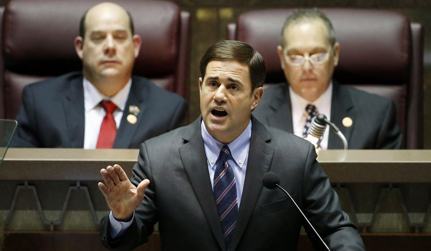 Arizona Republican Gov. Doug Ducey, front, gives his state-of-the-state address as Arizona House speaker David Gowan, left, and Arizona Senate President Andy Biggs, right, listen at the Arizona Capitol Monday, Jan. 12, 2015, in Phoenix. (AP Photo/Ross D. Franklin)