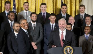 President Barack Obama reacts to San Antonio Spurs head basketball coach Gregg Popovich's, right, comments on stage as the president honored the 2014 NBA Champions the San Antonio Spurs basketball team during a ceremony in the East Room White House in Washington, Monday, Jan. 12, 2015. (AP Photo/Pablo Martinez Monsivais)
