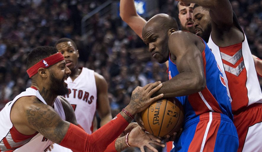 Toronto Raptors forward James Johnson, left, battles for the ball against Detroit Pistons forward Joel Anthony, right, during first half NBA basketball action in Toronto on Monday, Jan. 12, 2015. (AP Photo/The Canadian Press, Nathan Denette)