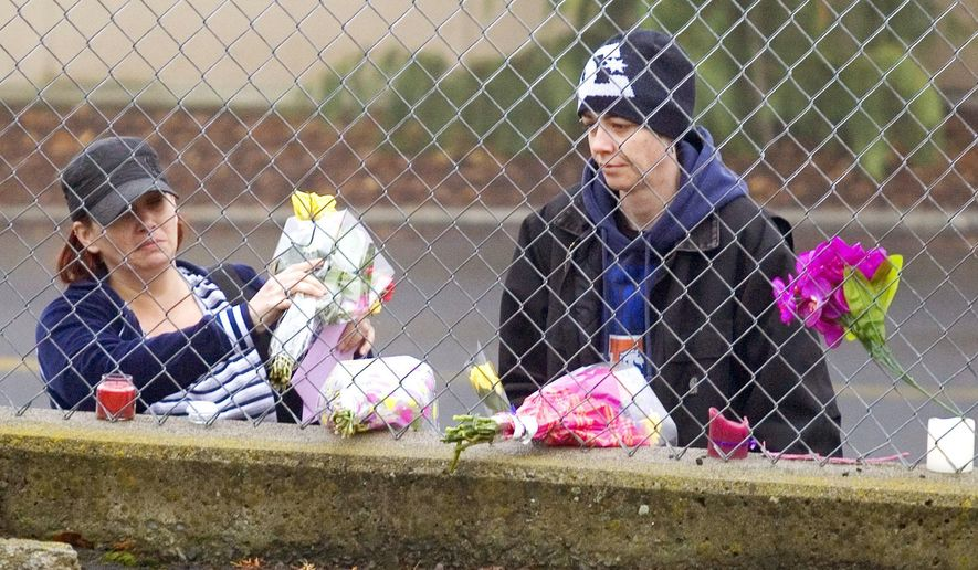 Unidentified mourners place flowers on a memorial for manager Belinda Niebuhr outside Arby's Restaurant in Moscow, Idaho, on Monday, Jan. 12, 2015 . Niebuhr died after being shot while at work on Saturday. (AP Photo/Moscow-Pullman Daily News, Geoff Crimmins)