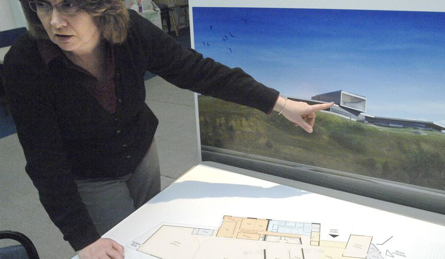 In this Jan. 8, 2015 photo, Beth Demke, executive director of the Gateway to Science Center in Bismarck, N.D., uses an artist's rendering to describe the many features of the proposed new $30 million science building located west of the Bismarck Community Bowl on a bluff overlooking the Missouri River. The project will enable the center to expand from a hands-on science facility for children into one for all ages. (APPhoto/Bismarck Tribune, Mike McCleary)