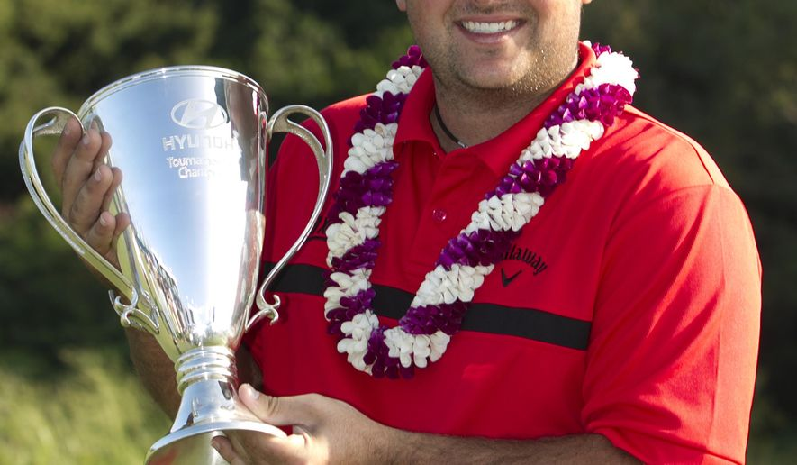 Patrick Reed holds the winning trophy after defeating Jimmy Walker in a playoff at the Tournament of Champions golf tournament, Monday, Jan. 12, 2015, in Kapalua, Hawaii.  (AP Photo/Marco Garcia)
