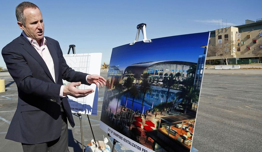 FILE - In this Monday, Jan. 5, 2015, file photo, Chris Meany, senior vice president of Hollywood Park Land Company, unveils an architectural rendering of a proposed NFL stadium at Hollywood Park in Inglewood, Calif. The developers behind a sprawling sports and housing complex in the Los Angeles suburbs, whose centerpiece stadium could become home for an NFL team, expect to receive as much as $100 million in local tax dollars over five years if it's completed, an Associated Press review has found. (AP Photo/Nick Ut, File)