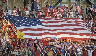 FILE - In this Oct. 16, 2012, file photo, United States soccer fans cheer as they unfurled a large American flag before a World Cup qualifying soccer match against Guatemala in Kansas City, Kan. The start of the final round of World Cup qualifying in North and Central America and the Caribbean will be moved up by three months to November 2016. Seeking its eighth straight World Cup berth, the United States has a bye until the fourth round, when it will be in a four-nation group with double match dates Nov. 7-17, 2015; March 21-29, 2016; and Aug. 29-Sept. 6, 2016.  (AP Photo/Reed Hoffmann, File)