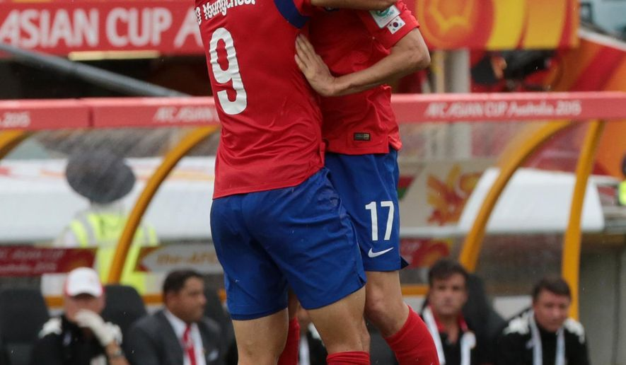South Korea's Cho Young Cheol, left, celebrates with teammate Lee Chung Yong after scoring a goal during the first round soccer match of the AFC Asia Cup between Korea and Oman in Canberra, Australia, Saturday, January 10, 2015. (AP Photo/Andrew Taylor)