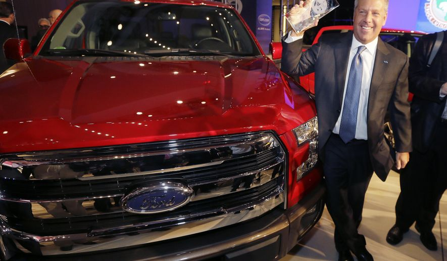Joe Hinrichs, Ford executive vice president and president, the Americas, poses with the Ford F-150 truck after winning the North American Truck of the Year during the North American International Auto Show, Monday, Jan. 12, 2015, in Detroit. (AP Photo/Carlos Osorio)