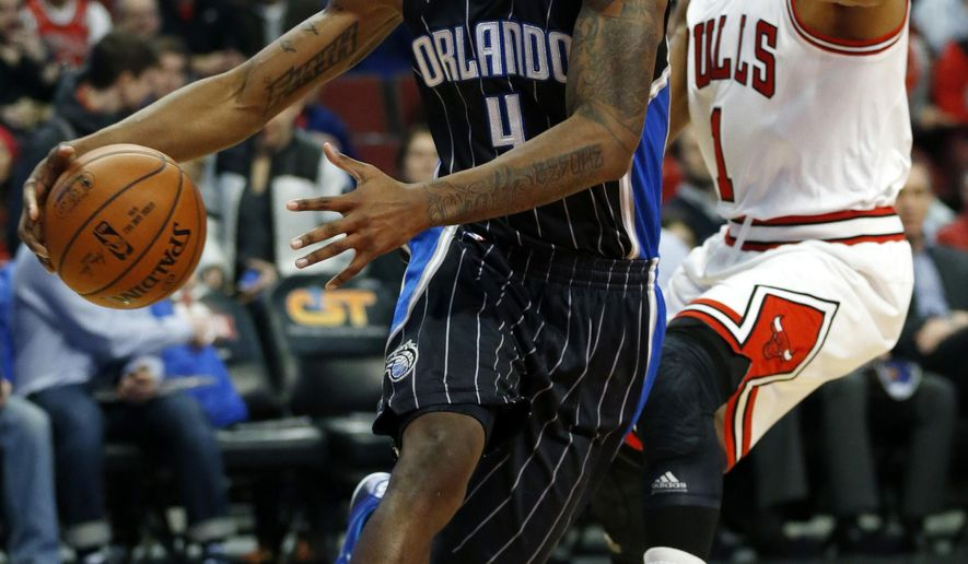 Orlando Magic guard Elfrid Payton (4) bolts past Chicago Bulls guard Derrick Rose (1) during the first half of an NBA basketball game on Monday, Jan. 12, 2015, in Chicago. (AP Photo/Andrew A. Nelles)