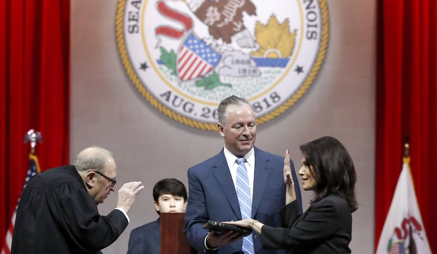 Illinois Lt. Gov.-elect Evelyn Sanguinetti, right, takes the oath of office from Judge Lewis V. Morgan, as her husband Raymond holds the Bible, Monday, Jan. 12, 2015, in Springfield, Ill. Sanguinetti becomes Illinois first Latina Lt. Governor. (AP Photo/Charles Rex Arbogast)