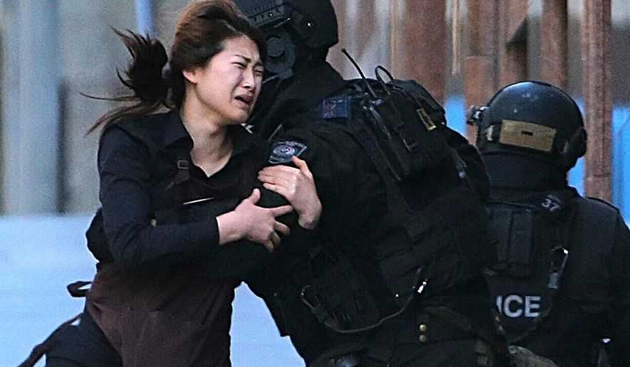 FILE - In this Dec. 15, 2014 file photo, a hostage runs to an armed tactical response police officers for safety after she escaped from a cafe under siege at Martin Place in the central business district of Sydney, Australia. Shotgun-wielding Man Haron Monis took 18 people hostage in the cafe; his 16-hour standoff ended when police stormed the cafe. Monis, 49, and two hostages died. The threat of Islamic extremism has justice officials balancing tougher law enforcement against the need to protect civil liberties, and that balance is struck in myriad ways around the world. (AP Photo/Rob Griffith, File)