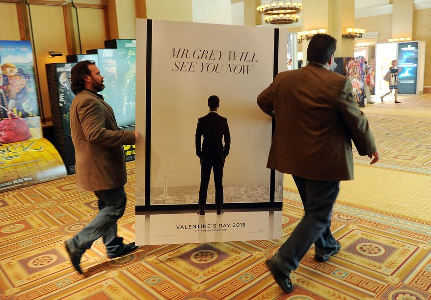 """Sheldon Domke, left, and Adam Mast move an advertisement for the upcoming film """"Fifty Shades of Grey"""" during a Las Vegas convention in 2014. The film is set for release on Feb. 13. (Photo by Chris Pizzello/Invision/AP)"""