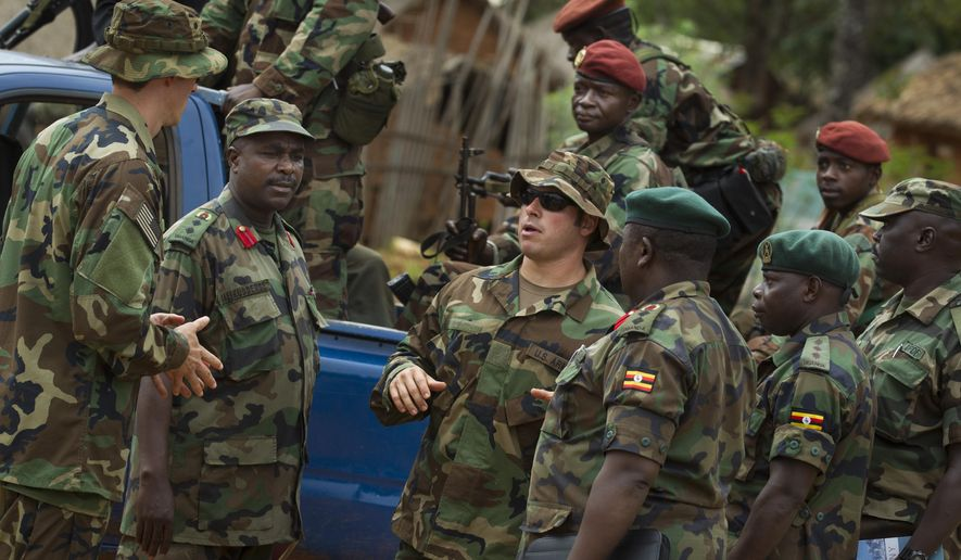 FILE - In this Sunday, April 29, 2012 file photo, U.S. Army special forces Master Sergeant Eric, centre, who would only give his first name in accordance with special forces security guidelines, speaks with troops from the Central African Republic and Uganda, in Obo, Central African Republic, where U.S. special forces have paired up with local troops and Ugandan soldiers to seek out Joseph Kony's Lord's Resistance Army (LRA). Uganda's government said Monday, Jan. 12, 2015, that it wants to try Lord's Resistance Army commander Dominic Ongwen, who recently surrendered to U.S. Forces and is in U.S. custody in Central African Republic, for war crimes and crimes against humanity, instead of at the International Criminal Court. (AP Photo/Ben Curtis, File)