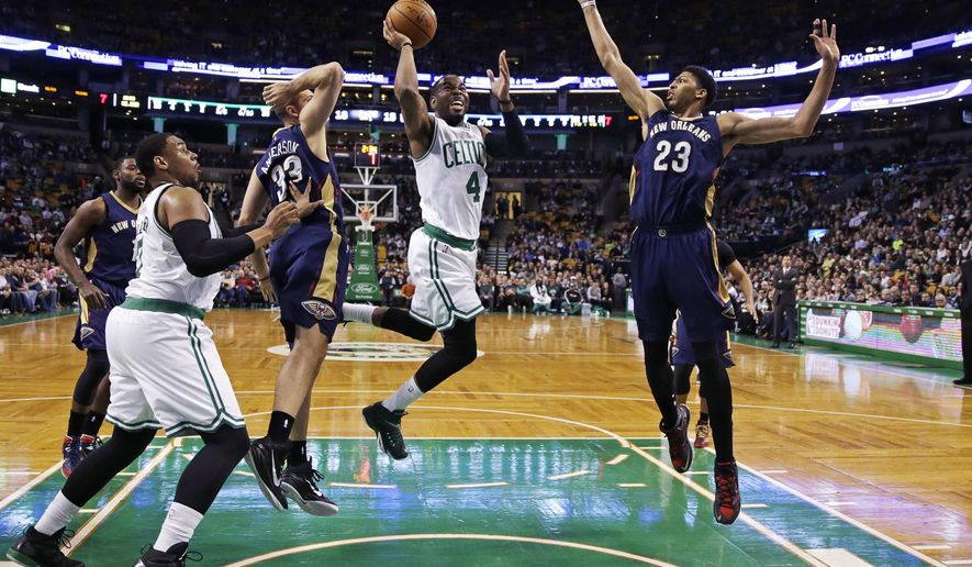 Boston Celtics guard Marcus Thornton (4) drives to the basket between New Orleans Pelicans forwards Anthony Davis (23) and Ryan Anderson (33) during the first quarter of an NBA basketball game in Boston, Monday, Jan. 12, 2015. (AP Photo/Charles Krupa)