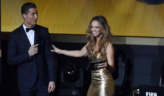 Cristiano Ronaldo, left, of Portugal fools around with presenter Kate Abdo during the FIFA Ballon d'Or 2014 gala held at the Kongresshaus in Zurich, Switzerland, Monday, Jan. 12, 2015. (AP Photo/KEYSTONE/Ennio Leanza)