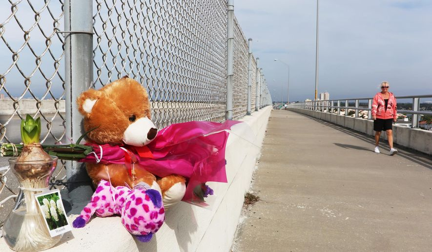 A pedestrian walks near a memorial for  Phoebe Jonchuck, 5, Friday, Jan. 9, 2015, that has been set up atop of the Dick Misener Bridge, St. Petersburg, Fla.,  Jonchuck was thrown from the bridge allegedly by her father John Jonchuck Jr. A Pinellas County judge appointed a public defender Monday, Jan 12, 2015, for John Jonchuck who is accused of throwing his 5-year-old daughter off a bridge. Police say 5-year-old Phoebe Jonchuck was likely alive when her father dropped her over a bridge railing, sending her into the waters of Florida's Tampa Bay.(AP Photo/Tampa Bay Times, Scott Keeler)