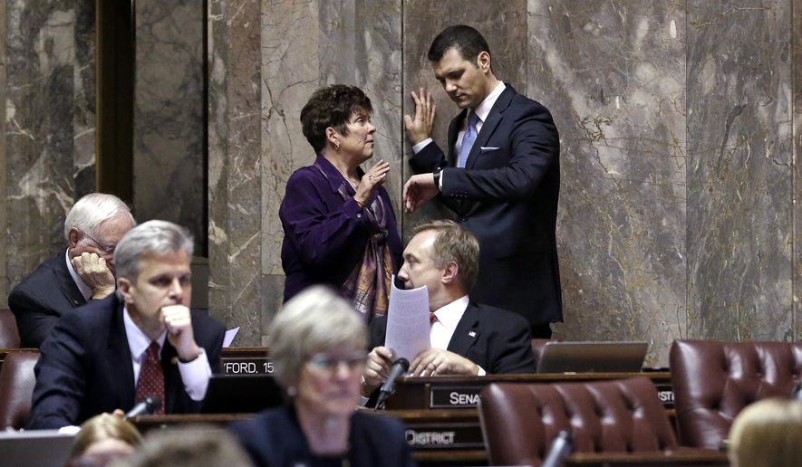 Republican senators Pam Roach, left, and Joe Fain, both of Auburn, Wash.,  talk moments before voting on a rule change that would make it harder for that chamber to take action on new taxes as the Washington state Legislature convened Monday, Jan. 12, 2015, in Olympia, Wash. The rule change would require a two-thirds vote of the Senate for any bill that creates a new tax in order to advance to the chamber floor for a final vote. (AP Photo/Elaine Thompson)