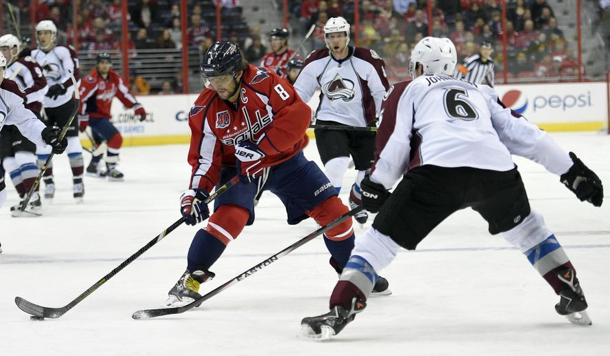 Washington Capitals left wing Alex Ovechkin (8), of Russia, skates with the puck against Colorado Avalanche defenseman Erik Johnson (6) during the first period of an NHL hockey game, Monday, Jan. 12, 2015, in Washington. (AP Photo/Nick Wass)