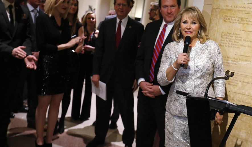 In this Saturday Jan. 10, 2015 photo, Oklahoma Gov. Mary Fallin, right, speaks as her husband, Wade Christensen, second from right, and Tulsa Mayor Dewey Bartlett, center, listen at the Philbrook Museum of Art in Tulsa, Okla. for a pre-inaugural event. (AP Photo/Tulsa World, James Gibbard)  ONLINE OUT; KOTV OUT; KJRH OUT; KTUL OUT; KOKI OUT; KQCW OUT; KDOR OUT; TULSA OUT; TULSA ONLINE OUT