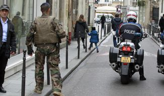 Police officers and soldiers patrol Rue Pavee, in the heart of the Paris Jewish quarter, Monday Jan. 12, 2015. France on Monday ordered 10,000 troops into the streets to protect sensitive sites after three days of bloodshed and terror, amid the hunt for accomplices to the attacks that left 17 people and the three gunmen dead. (AP Photo/Remy de la Mauviniere)
