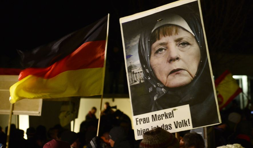 A protestor holds a poster with an image of German Chancellor Angela Merkel wearing a headscarf in front of the Reichstag building with a crescent on top during a rally of the group Patriotic Europeans against the Islamization of the West, or PEGIDA, in Dresden, Germany, Monday, Jan. 12, 2015. (AP Photo/Jens Meyer)