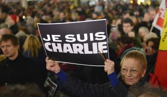 """A woman shows a banner reading """"I am Charlie"""" for the victims of the shooting at the satirical newspaper Charlie Hebdo in Paris during a demonstration of thousands against the right wing PEGIDA movement, """"Patriotic Europeans against the Islamization of the West"""" in Duesseldorf, Germany, Monday evening, Jan. 12, 2015.  (AP Photo/Martin Meissner)"""