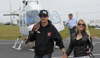 FILE - In this May 17, 2014 file photo, Kurt Busch walks with his girlfriend, Patricia Driscoll, after arriving for the NASCAR Sprint All-Star auto race at Charlotte Motor Speedway in Concord, N.C. A hearing on Busch's ex-girlfriend's request for a no-contact order stemming from assault allegations resumed Monday in Dover, Del. Busch's attorneys have denied Driscoll's assault allegations and have tried to portray Driscoll as a scorned woman out to destroy Busch's career. (AP Photo/Terry Renna, File)