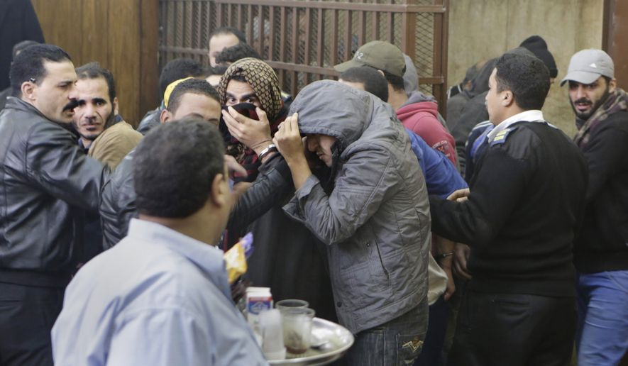 Men who were arrested in a televised raid last month by police looking for gays at a Cairo public bathhouse, hide their faces after an Egyptian court acquitted them in Cairo, Egypt, Monday, Jan. 12, 2015. (AP Photo/Amr Nabil)