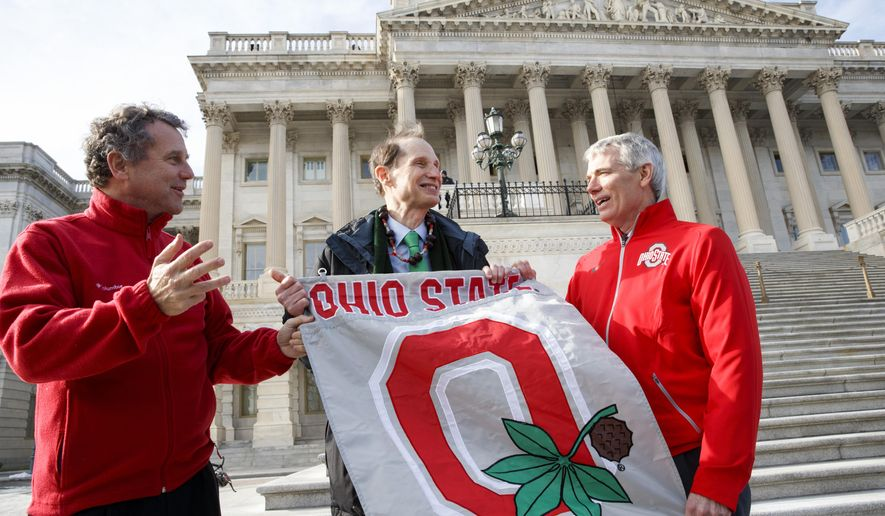 Ohio State Buckeye fans Sen. Sherrod Brown, D-Ohio, left, and Sen. Rob Portman, R-Ohio, right, have some fun with Sen. Ron Wyden, D-Ore., center, an Oregon Ducks fan, on the steps of the Senate on Capitol Hill in Washington, Tuesday, Jan. 13, 2015, on the day after Ohio State University defeated the University of Oregon 42-20 in the inaugural college football playoff final, 42-20.  (AP Photo/J. Scott Applewhite)