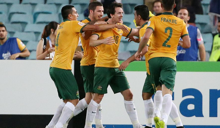 Australia's Robbie Kruse, center, is congratulated by teammates after scoring a goal during the AFC Asian Cup soccer match between Australia and Oman in Sydney, Australia, Tuesday, Jan. 13, 2015. (AP Photo/Rob Griffith)