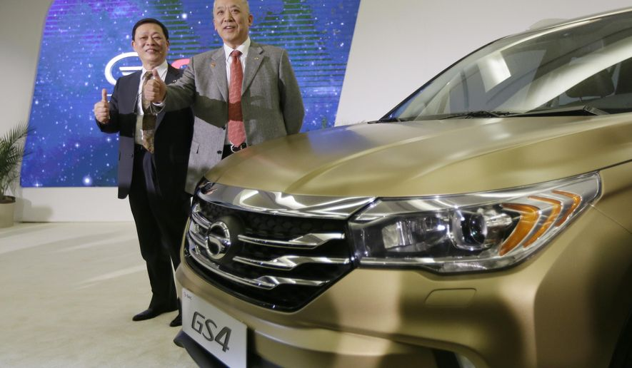 Xiangdong Huang, president of GAC Engineering, left, and Yuan Zhongrong, vice chairman of GAC, pose with the automaker's new GS4 during the North American International Auto Show, Monday, Jan. 12, 2015 in Detroit. (AP Photo/Carlos Osorio)