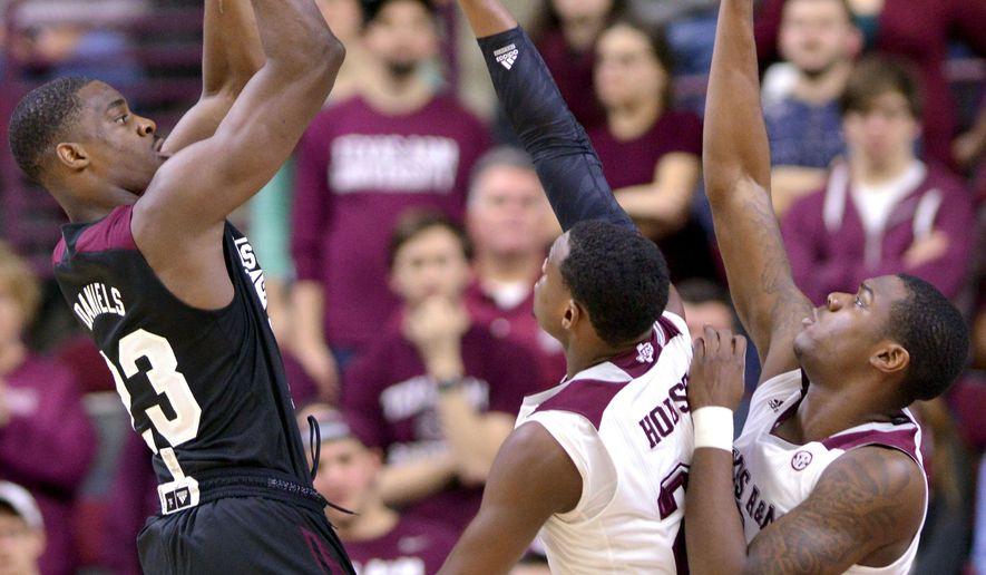 Mississippi State guard Travis Daniels (23) gets a shot off over the hands of Texas A&M's Danuel House (23) and Jalen Jones (12) Tuesday, Jan. 13, 2015 during the first of a men's NCAA college basketball game at Reed Arena in College Station, Texas.  (AP Photo/The Bryan-College Station Eagle, Sam Craft)