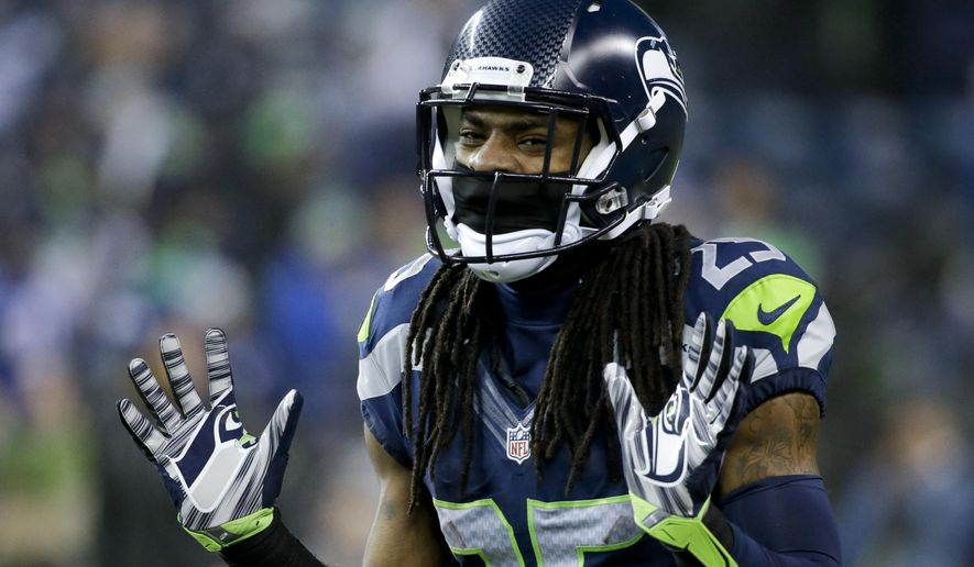 FILE - In this Jan. 10, 2015, file photo, Seattle Seahawks cornerback Richard Sherman gestures during warmups before an NFL divisional playoff football game against the Carolina Panthers in Seattle. Whether by design or coincidence, Aaron Rodgers didn't throw in cornerback Richard Sherman's direction in the teams' first meeting this season.  (AP Photo/Elaine Thompson, File)