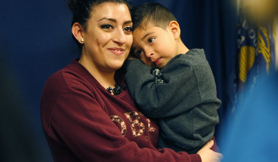 Elizabeth Barrios holds her son Aiden Ngo during a news conference at the Francom Public Safety Center in Ogden, Utah, Tuesday, Jan. 13, 2015.  Authorities say Elizabeth Barrios left her car unlocked and running as she dropped off another child at day care. When she walked out, she saw someone driving her car away with her son inside. Police arrived and called her cellphone, which was in the car, hoping to reach the thief and negotiate the boy's release, said Lt. Tim Scott. Instead, Aiden answered the phone. He told officers that he was alone after the thief left the car and ran away, but he didn't know where he was. (AP Photo/The Deseret News, Chelsey Allder)  SALT LAKE TRIBUNE OUT;  MAGS OUT