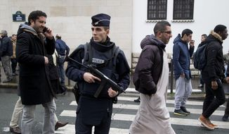 In this Friday Jan. 9, 2015, file photo, a French police officer stands guard outside the Grand Mosque as people arrive for Friday prayers, Paris. Firebombs and pigs' heads are being tossed at mosques and women in veils have been insulted in a surge of anti-Muslim acts since last week's murderous assault on the newsroom of a satirical Paris paper, according to a Muslim who tracks such incidents in France. (AP Photo/Michel Euler, File)
