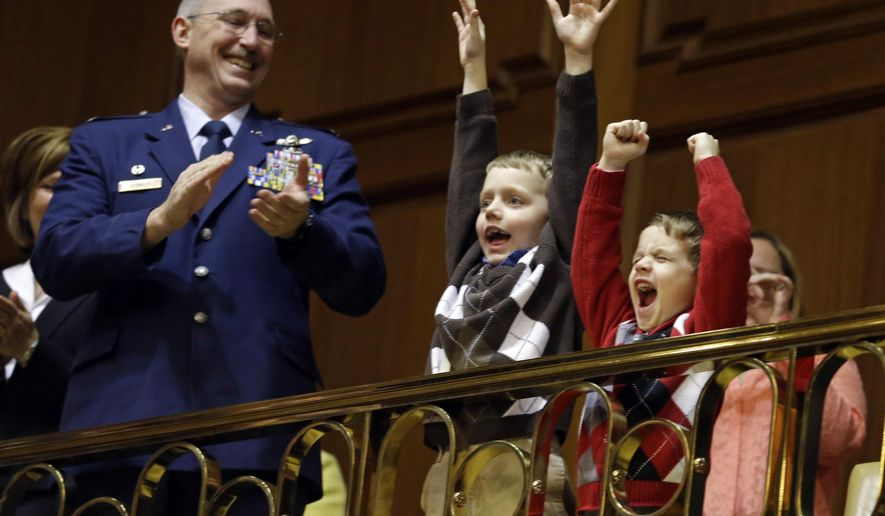 Col. Patrick Renwick of the Indiana Air Nation Guard's 122nd Fighter Wing in Fort Wayne, Ind., looks on as Jacen Troxel, 8, and his brother Ben Troxel, 5, cheer as they were introduce by Indiana Gov. Mike Pence during his State of the State address to a joint session of the legislature at the Statehouse in Indianapolis, Tuesday, Jan. 13, 2015. The boys, sons of an Indianapolis Metropolitan Police Department detective, raised more than $20,000 to purchase bulletproof plates for the department's officers.  (AP Photo/Michael Conroy)