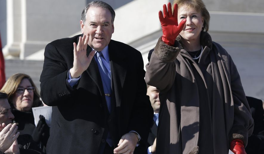 Former Arkansas Gov. Mike Huckbee, left, and his wife Janet wave as they are recognized at Arkansas Gov. Asa Hutchinson's inauguration ceremony at the Arkansas state Capitol in Little Rock, Ark., Tuesday, Jan. 13, 2015. (AP Photo/Danny Johnston)