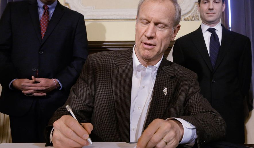 Illinois Gov. Bruce Rauner signs ethics legislation in his office at the Illinois State Capitol, Tuesday, Jan. 13, 2015, in Springfield, Ill. (AP Photo/Seth Perlman)