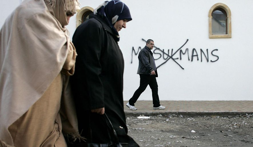 "FILE - In this Monday Feb. 8, 2010 file photo, Muslim residents walk past racial slurs painted on the walls of a mosque in the town of Saint-Etienne, central France. Graffiti reads: ""Muslims"". Firebombs and pigs' heads are being tossed at mosques and women in veils have been insulted in a surge of anti-Muslim acts since last week's murderous assault on the newsroom of a satirical Paris paper, according to a Muslim who tracks such incidents in France. France's large Muslim population risks becoming collateral damage in the aftermath of the three attacks by French radical Islamists who killed 17 people. Muslims in other European countries also won't be spared, some Muslim leaders and experts say. Concern about a backlash against Muslims was discussed Monday Jan. 13, 2015, during a meeting on counter-terrorism measures at the Interior Ministry. (AP Photo/Laurent Cipriani, File)"