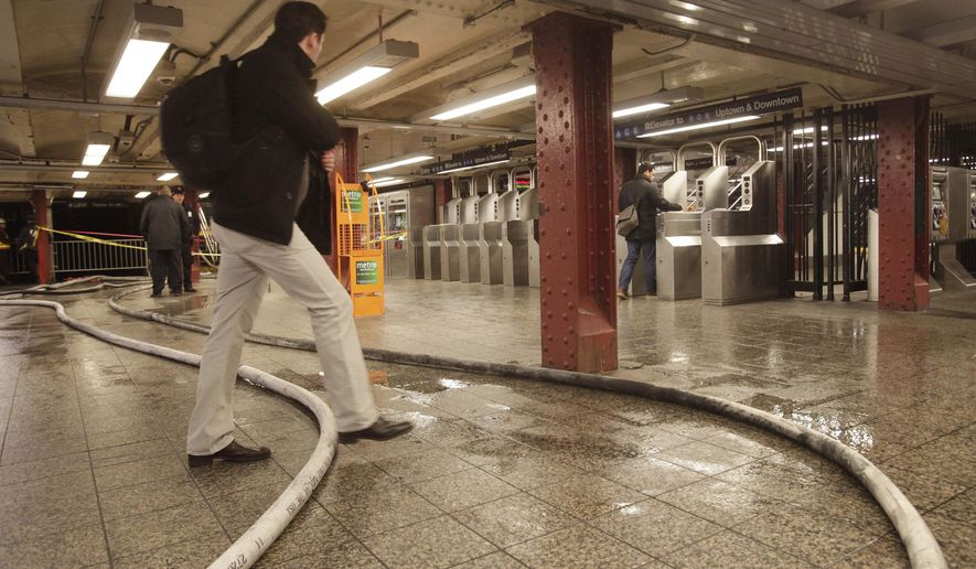 A commuter steps over a fire hose in New York's Penn Station, early Tuesday, Jan. 13, 2015. Commuters experienced some delays following an early morning fire in an underground construction site at 34th Street and Eighth Avenue that disrupted train service. (AP Photo/Mark Lennihan)