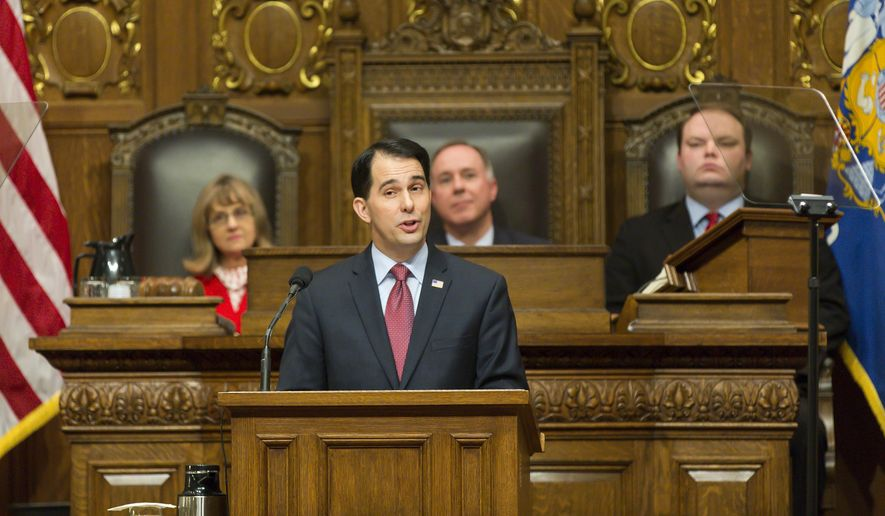 Wisconsin Gov. Scott Walker, center front, addresses a joint session of the state Legislature during the Governor's State of the State speech in the Assembly chambers at the state Capitol, Tuesday, Jan. 13, 2015, in Madison, Wis. Behind is Senate President Mary Lazich, R-New Berlin, left, Assembly Speaker Robin Vos, left, R-Burlington, and Assembly Speaker Pro Tempore Tyler August, right, R-Lake Geneva. (AP Photo/Andy Manis)