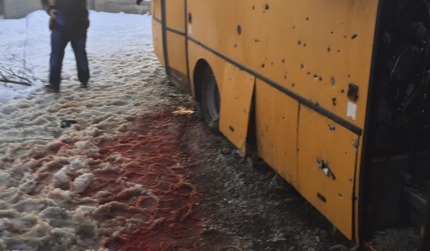 In this photo provided by the Ukrainian Interior Ministry, a man walks past snow covered with blood as he passes by a bus destroyed by a rebel shell at the checkpoint near the town of Volnovakha in the Donetsk region, eastern Ukraine, Tuesday, Jan. 13, 2015. At least 10 civilians were killed and a further 13 wounded as the bus was hit by a pro-Russian separatists' shell while passing through the checkpoint, local officials said. (AP Photo/Ukrainian Interior Minis
