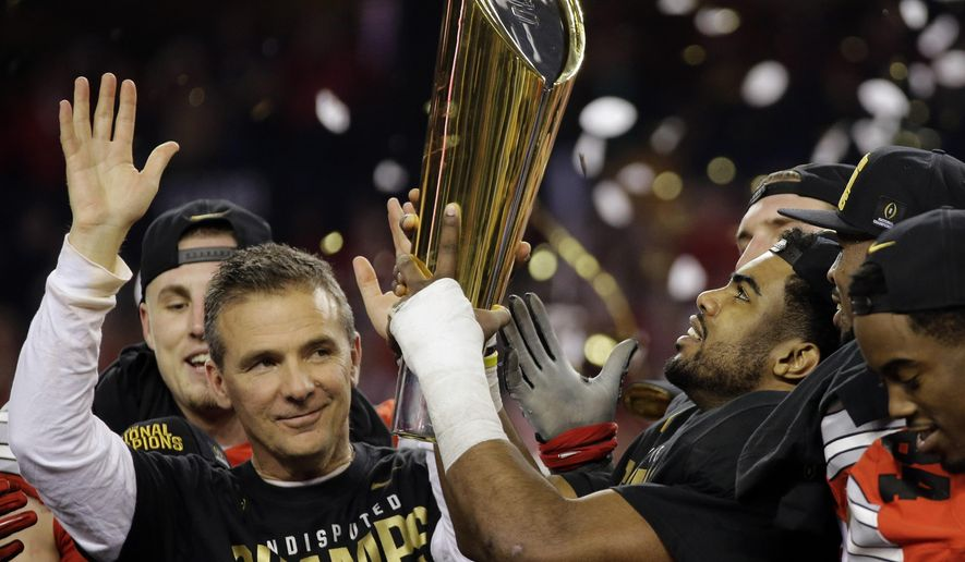 Ohio State head coach Urban Meyer and Ezekiel Elliott celebrate after the NCAA college football playoff championship game against Oregon Monday, Jan. 12, 2015, in Arlington, Texas. Ohio State won 42-20. (AP Photo/Eric Gay)