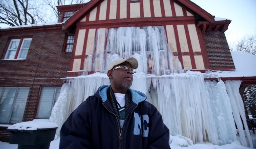 Home owner E.T. Williamson Sr. stands in front of the frozen section of his house in Detroit on Monday, Jan.12, 2015. Williamson Sr. says a pipe on the third floor of the house burst several days ago, causing water to pour through the walls and into the basement. Temperatures in the Detroit area have been below zero, causing the steady flow of water to freeze.  Williamson says he lost the home in tax foreclosure, but his clothing and other belongings still were inside. (AP Photo/Detroit Free Press, Kirthmon F. Dozier)  DETROIT NEWS OUT;  NO SALES