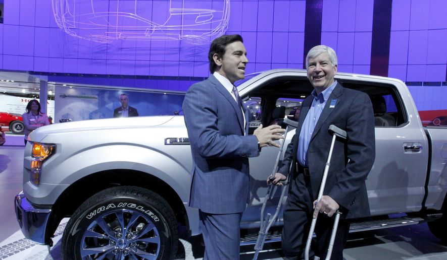 Mark Fields, President and chief Executive Officer of Ford, left, talks with Michigan Gov. Rick Snyder at the Ford exhibit during the North American International Auto Show Tuesday, Jan. 13, 2015, in Detroit. (AP Photo/Detroit Free Press, Diane Weiss)  DETROIT NEWS OUT;  NO SALES