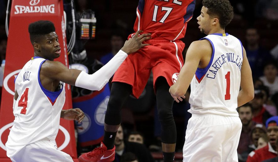 Atlanta Hawks' Dennis Schroder (17), of Germany, passes the ball between Philadelphia 76ers' Nerlens Noel (4) and Michael Carter-Williams (1) during the first half of an NBA basketball game, Tuesday, Jan. 13, 2015, in Philadelphia. (AP Photo/Matt Slocum)