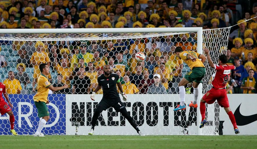 Australia's Trent Sainsbury heads the ball across the goal as Oman's goalkeeper Ali Al Habsi centre watches during the AFC Asian Cup soccer match between Australia and Oman in Sydney, Australia, Tuesday, Jan. 13, 2015. (AP Photo/Rob Griffith)