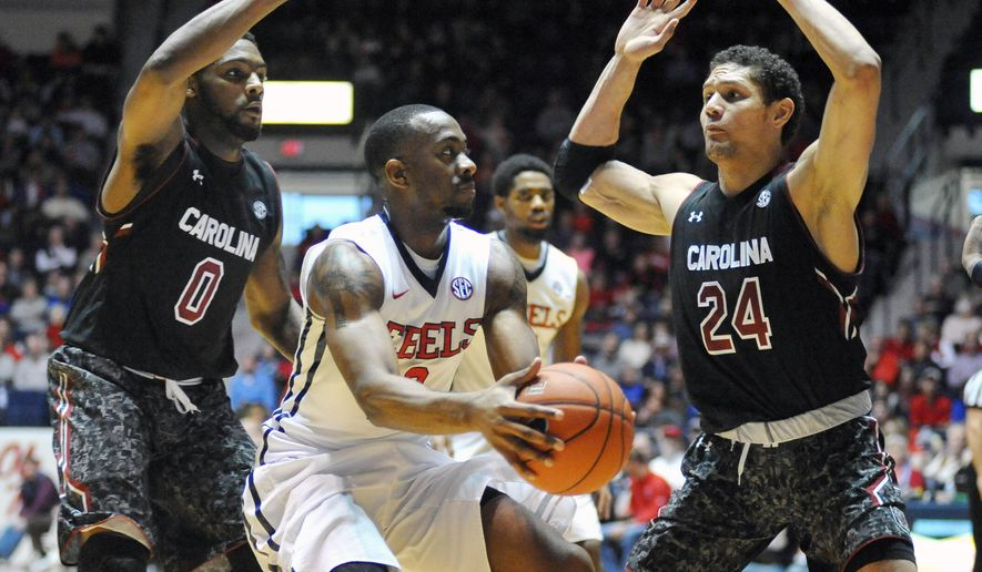Mississippi guard Ladarius White (10) is defended by South Carolina guard Sindarius Thornwell (0) and forward Michael Carrera (24) during an NCAA college basketball game in Oxford, Miss., Saturday, Jan. 10, 2015. (AP Photo/The Oxford Eagle, Bruce Newman) MAGAZINES OUT; NO SALES; MANDATORY CREDIT