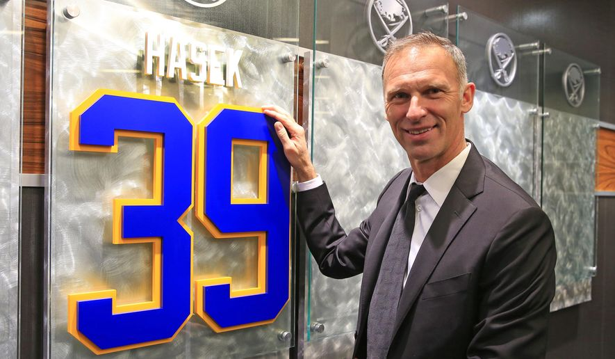 Former Buffalo Sabre Dominik Hasek, of The Czech Republic,  stands next to a plaque with his newly retired  number in the enterance way to the Buffalo Sabres lockeroom prior to their NHL hockey game against the Detroit Red Wings at the First Niagara Center on Tuesday, Jan. 13, 2015., in Buffalo, N.Y.  (AP Photo/The Buffalo News, Harry Scull, Jr.)  TV OUT; MAGS OUT; MANDATORY CREDIT; BATAVIA DAILY NEWS OUT; DUNKIRK OBSERVER OUT; JAMESTOWN POST-JOURNAL OUT; LOCKPORT UNION-SUN JOURNAL OUT; NIAGARA GAZETTE OUT; OLEAN TIMES-HERALD OUT; SALAMANCA PRESS OUT; TONAWANDA NEWS OUT