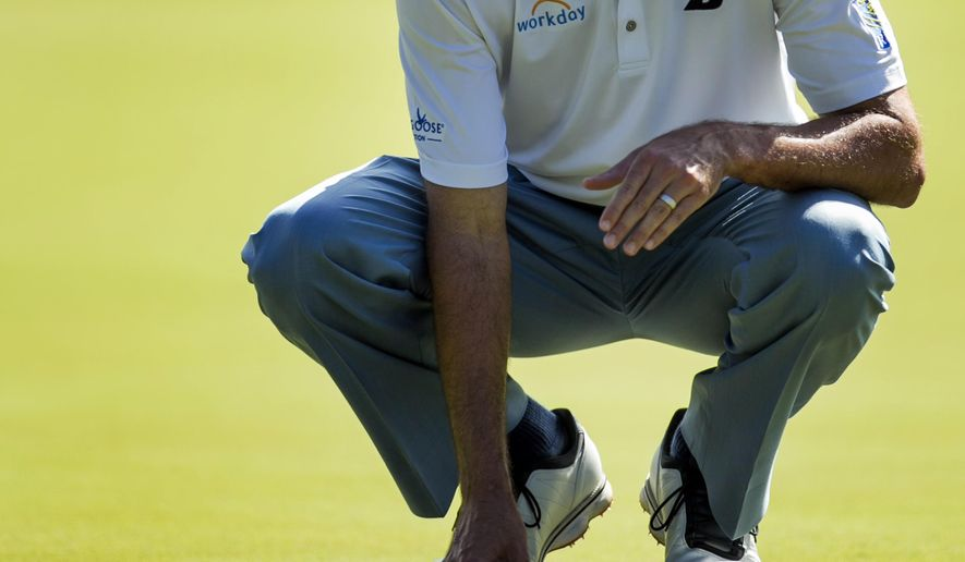 Matt Kuchar lines up his putt on the first green during the third round of the Tournament of Champions golf tournament, Sunday, Jan. 11, 2015, in Kapalua, Hawaii. (AP Photo/Marco Garcia)